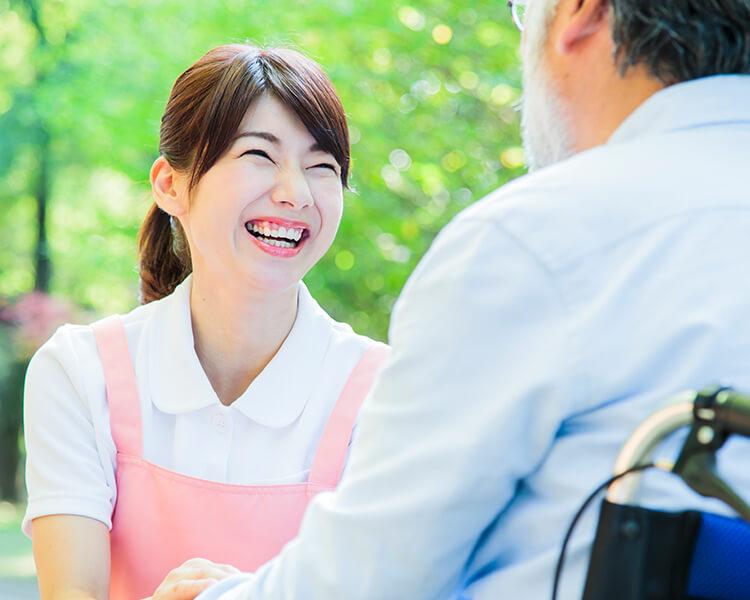 笑顔で介護を行う女性介護職員