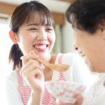 利用者の食事を手伝う女性介護職員